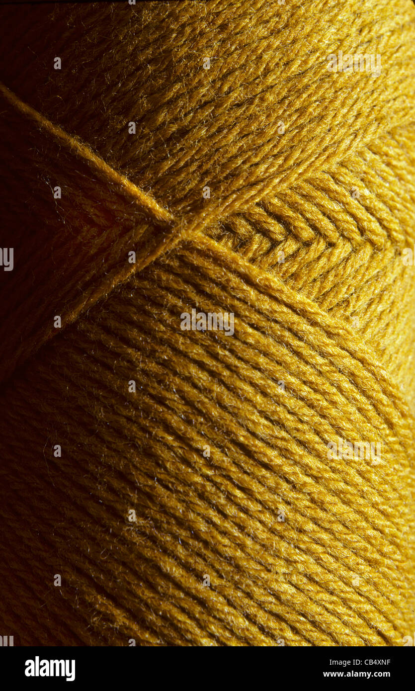 Close-up of a skein of gold wool knitting yarn - Stock Image