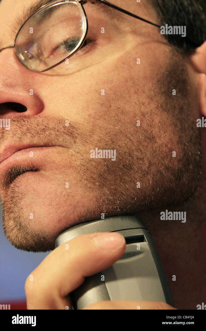a man shaving his chin with a silver electric razor Stock Photo