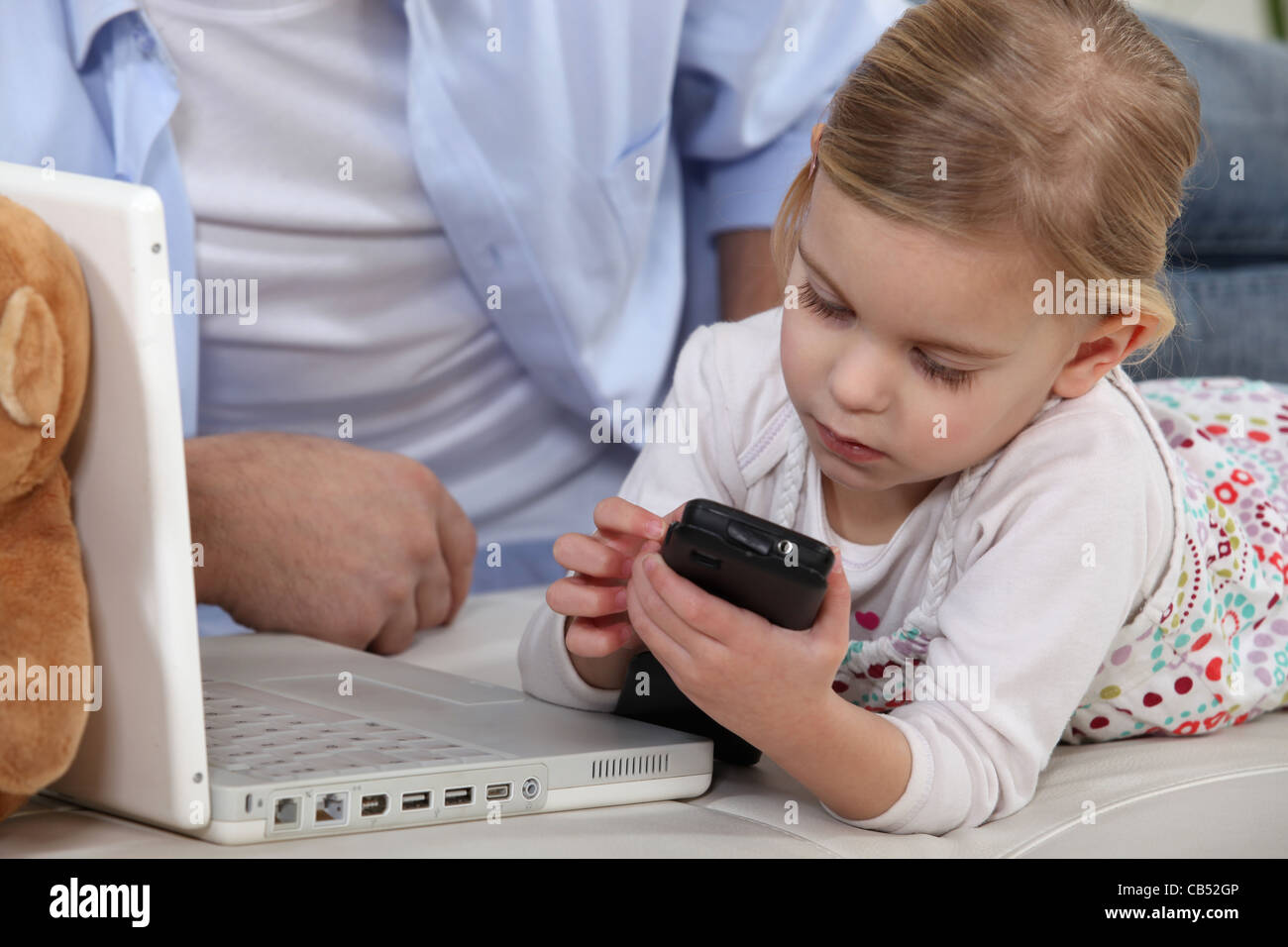 Young child playing with her father's mobile phone - Stock Image
