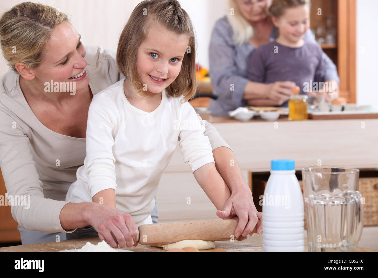 Little girls and their mums making cakes - Stock Image