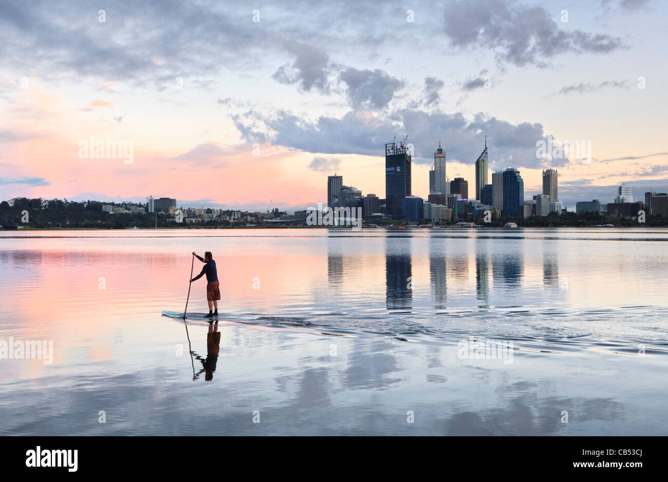 Paddle surfer on the river at sunrise with the city skyline in the distance. - Stock Image