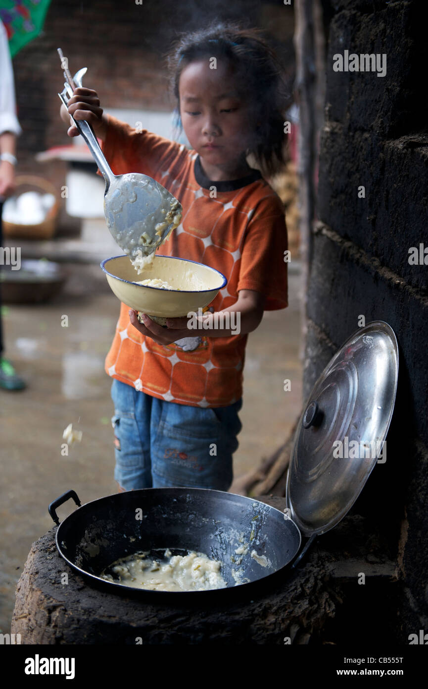 A stay-at-home girl fills a bowl with rice for lunch in remote poor Tumen village, Shangluo, Shanxi province, China. - Stock Image