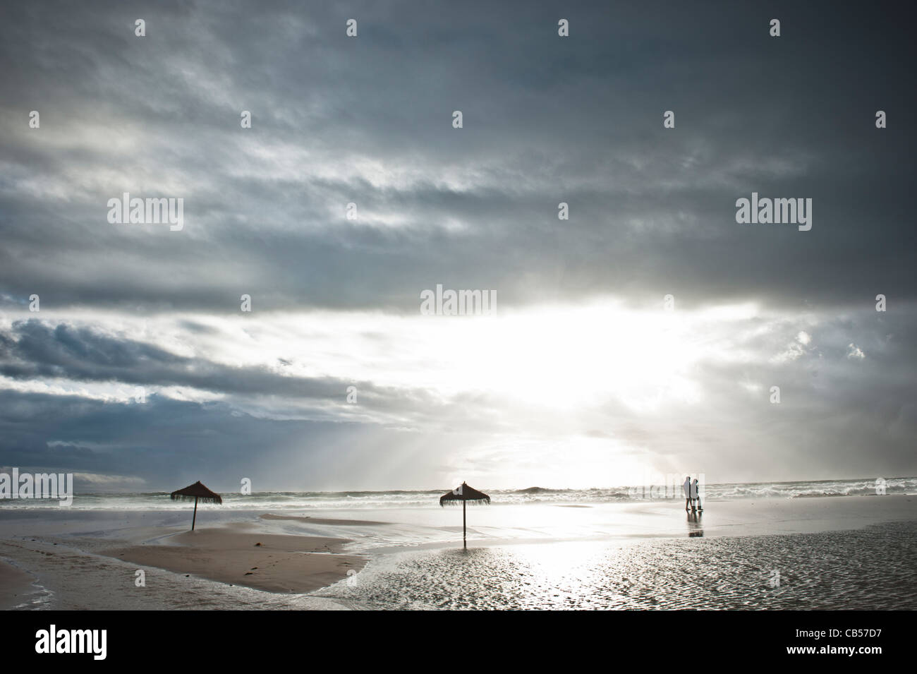 A couple walking on a deserted beach with stormy weather, Tarifa, Andalusia, Spain - Stock Image