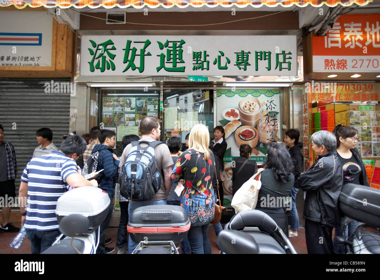 people waiting outside the original one dim sum tim ho wan michelin starred restaurant in mong kok district kowloon - Stock Image