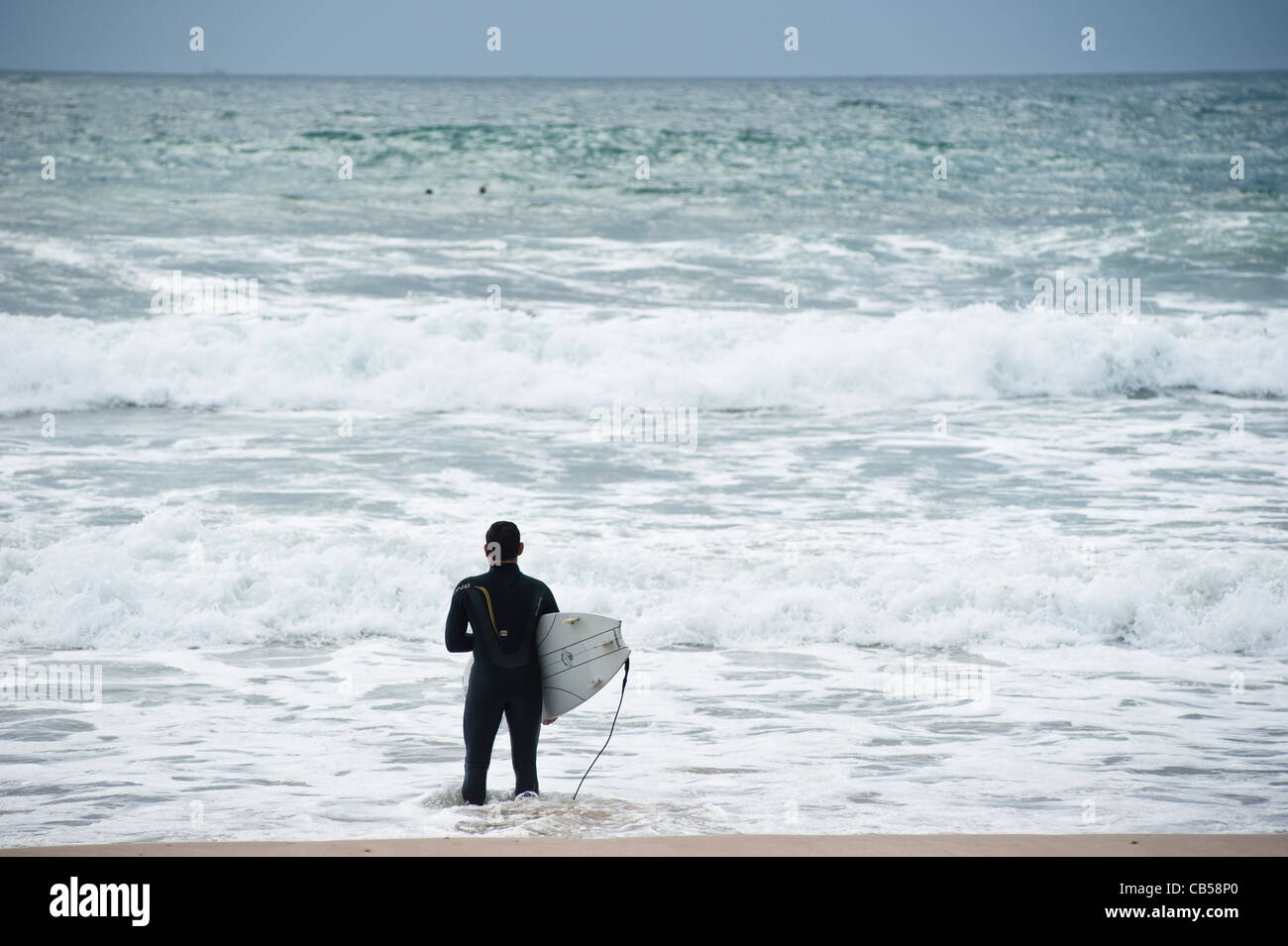 Surfer observing the waves before going into the water, Tarifa, Andalusia, Spain - Stock Image