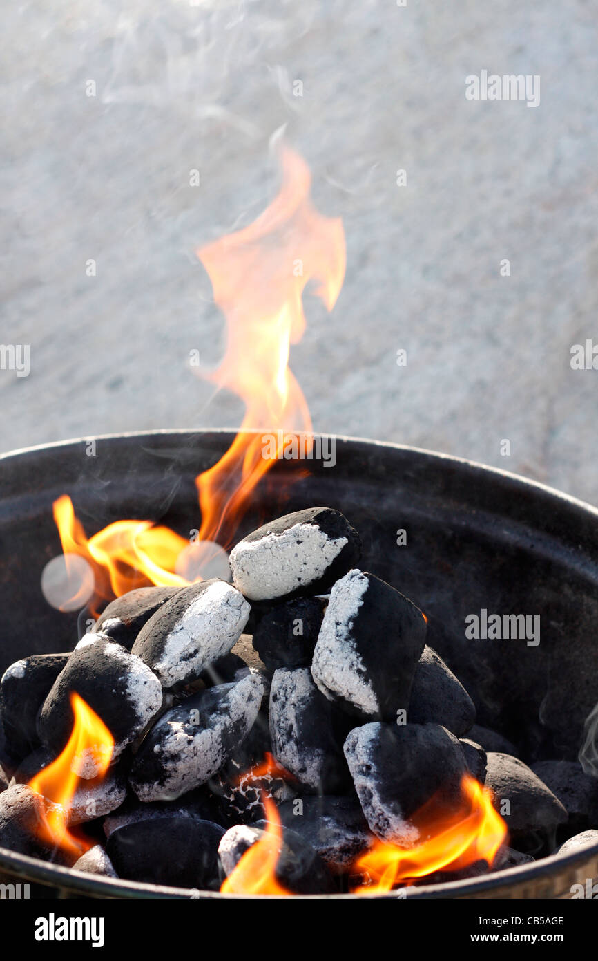 A grill with charcoal and flames - Stock Image