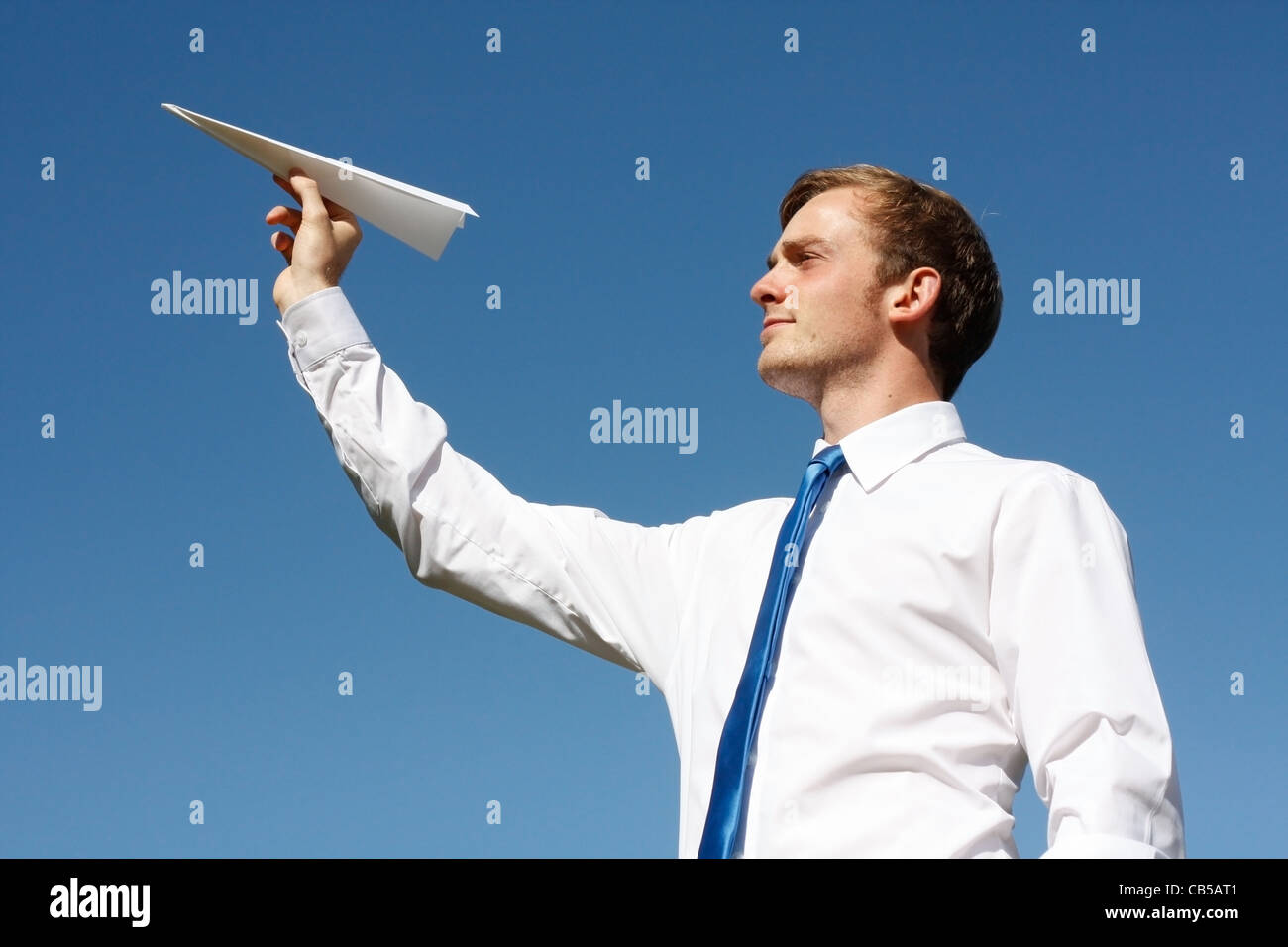 A business man throwing a paper plane - Stock Image