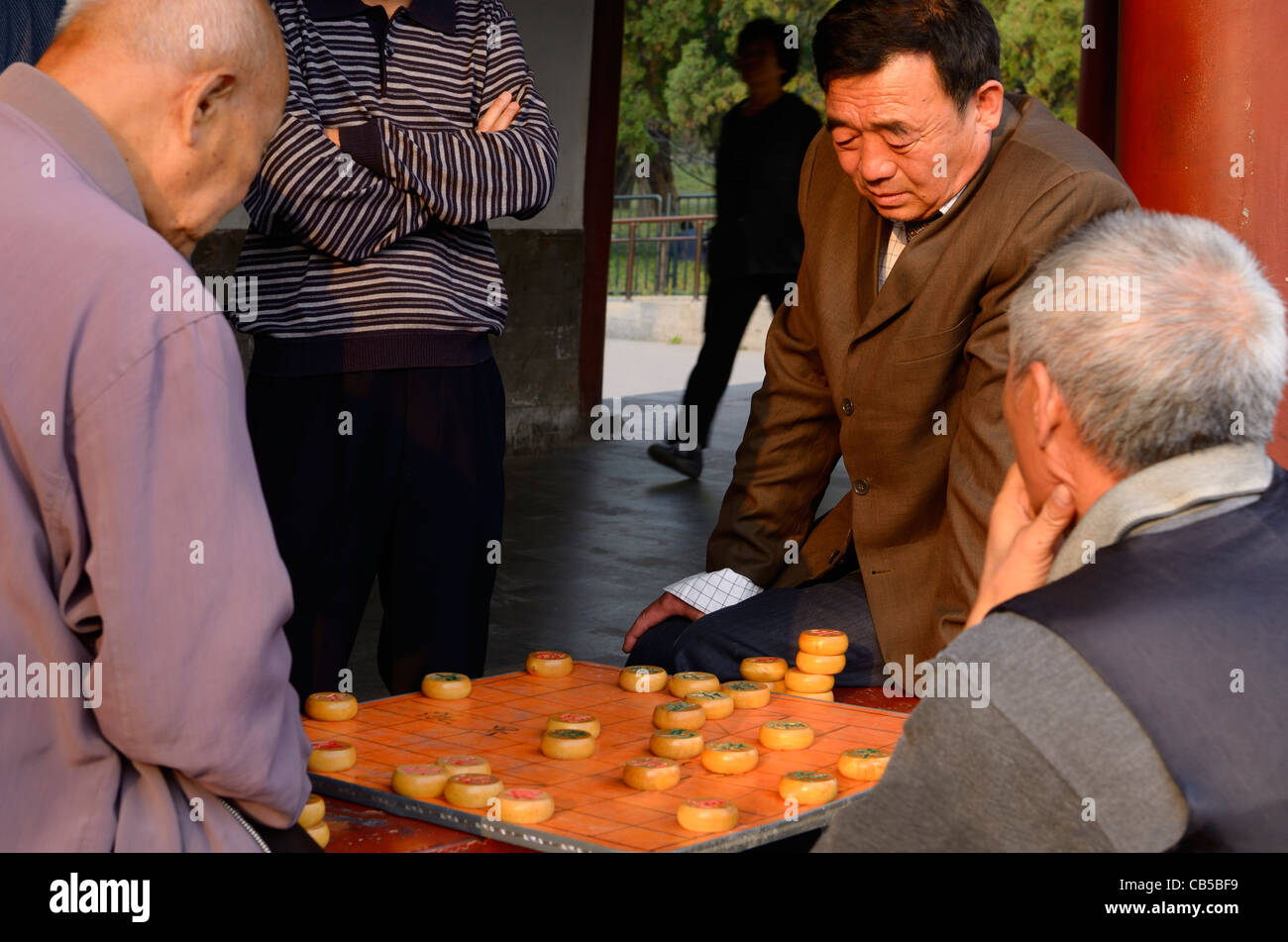 Group of men watching pair play Chinese Chess or Xiangqi in Beijing Peoples Republic of China - Stock Image