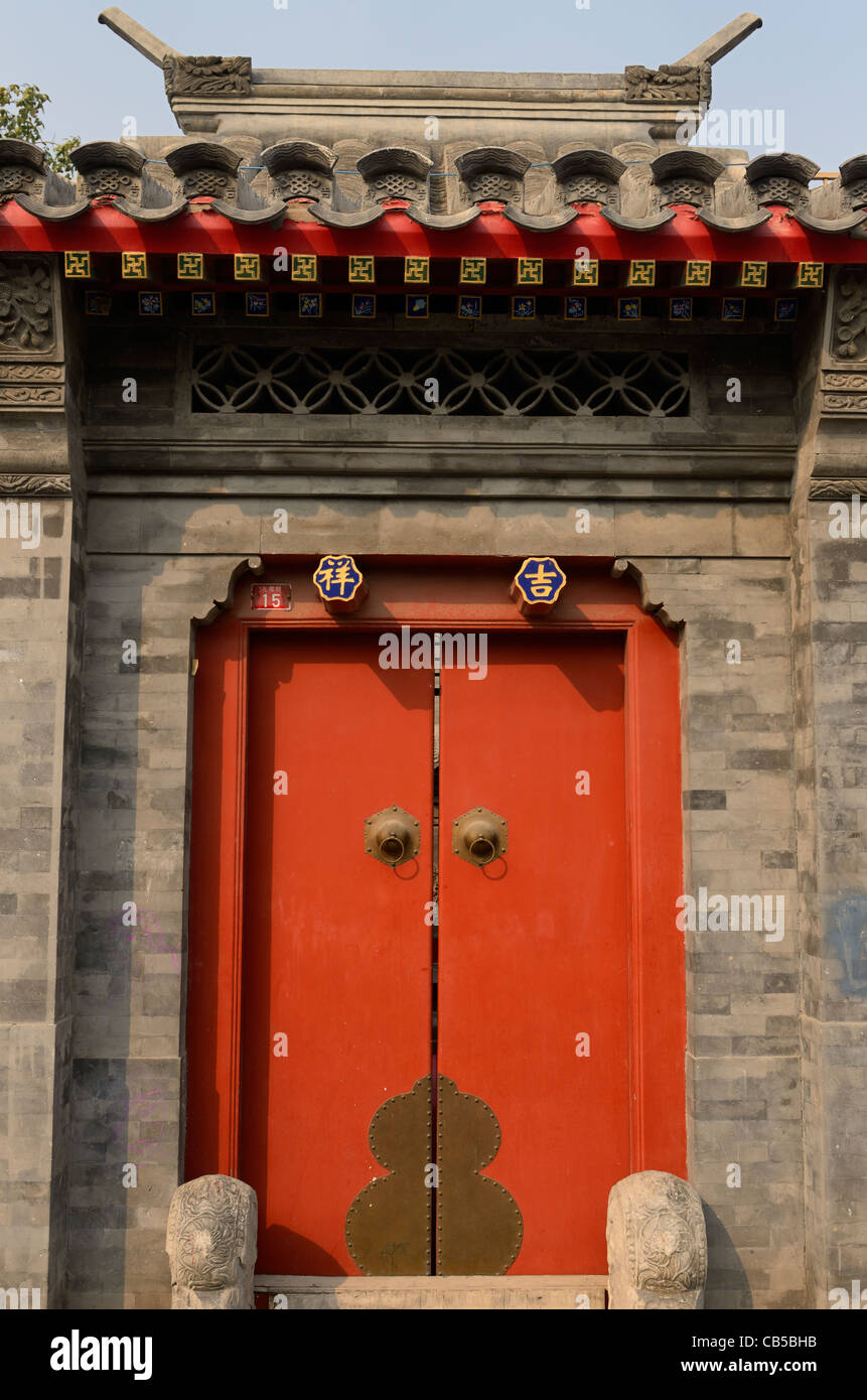 Red door and stonework at estate in Shichahai area hutong in Beijing Peoples Republic of China Stock Photo