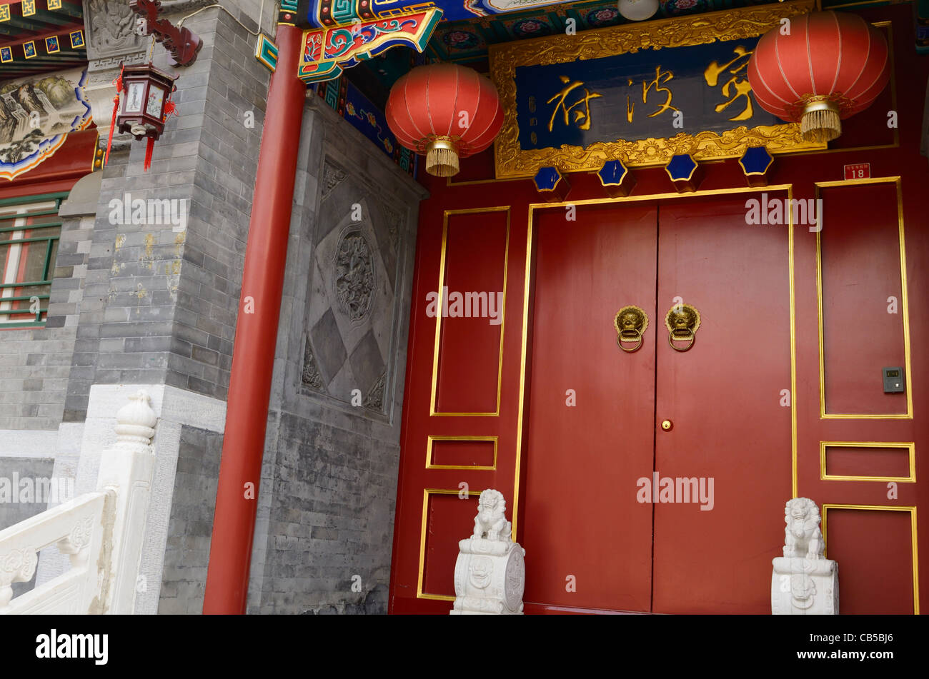 Red door with ornaments at luxury estate in Shichahai area hutong in Beijing Peoples Republic of China Stock Photo