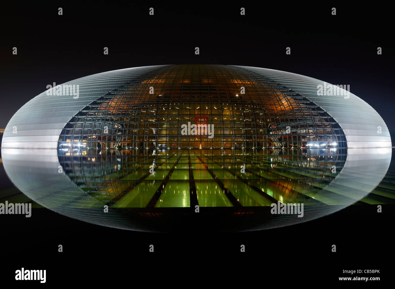 National Centre for the Performing Arts egg lit at night and reflected in water of pool Beijing Peoples Republic Stock Photo
