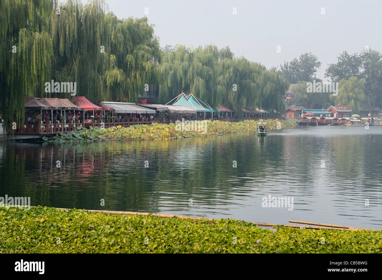 Willow trees and restaurants along Qianhai Lake in the Shichahai area of Beijing China - Stock Image