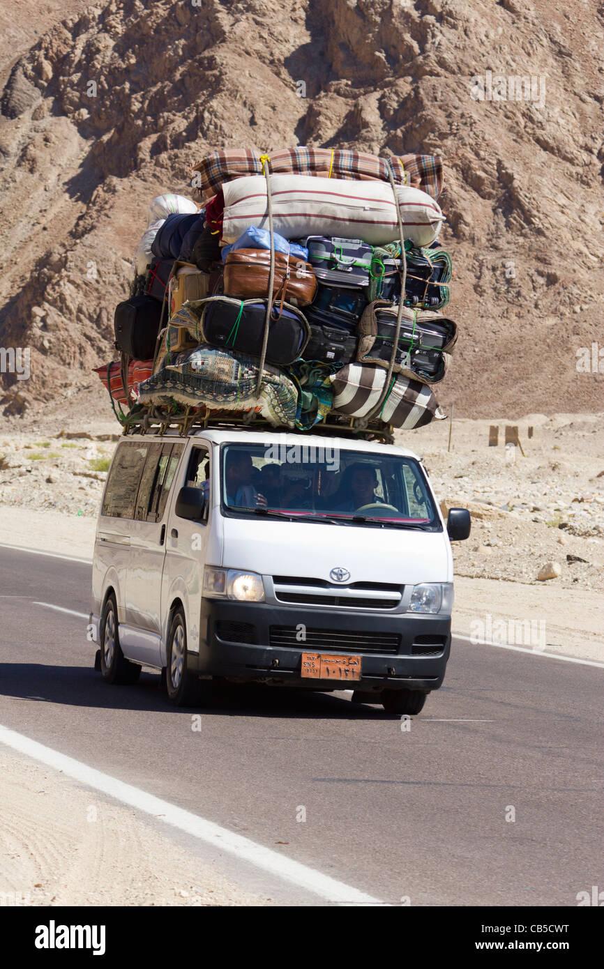 overladen minibus on the road from Nuweiba to Cairo, Sinai Peninsula, Egypt - Stock Image
