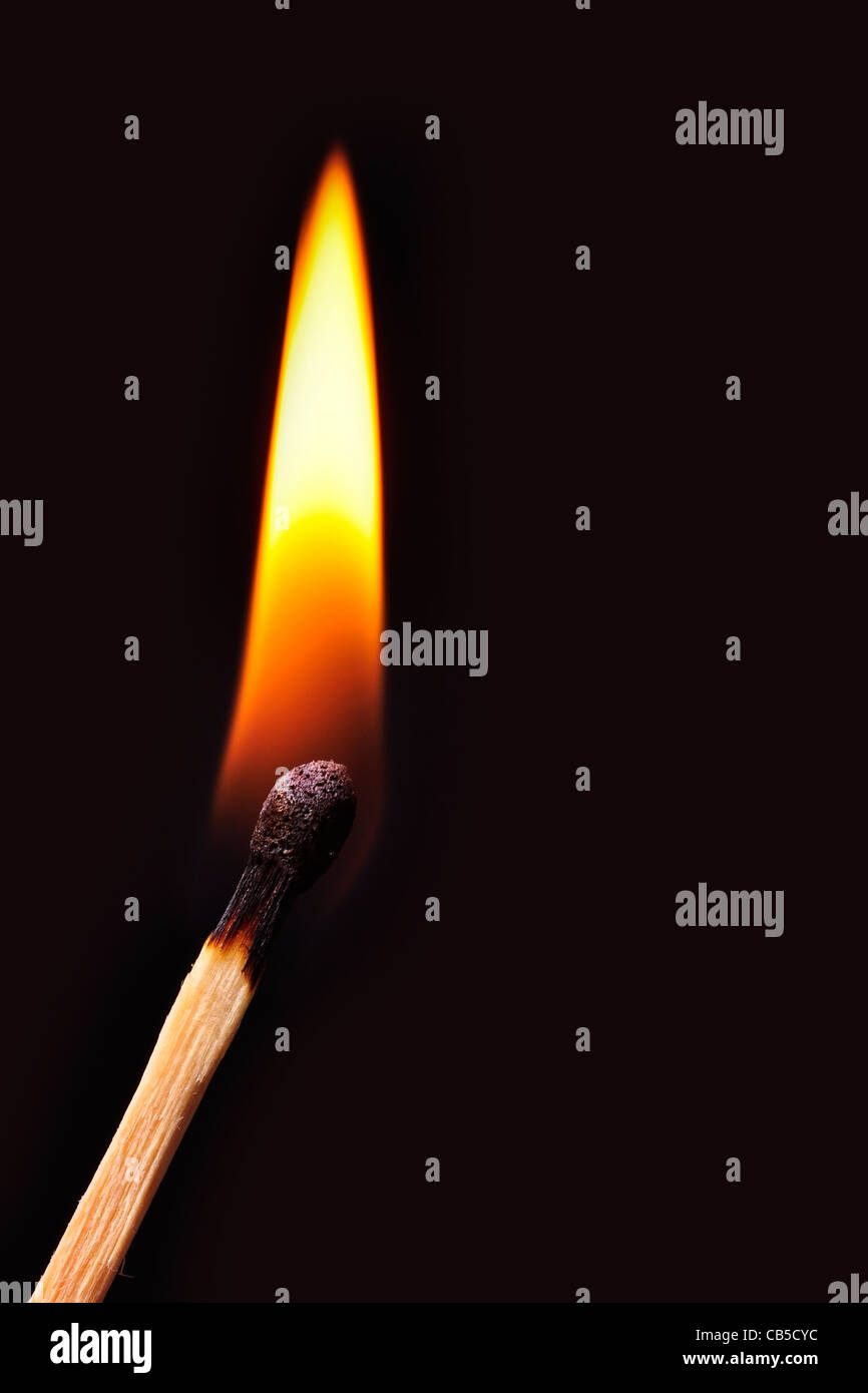Match burns in a black background - Stock Image