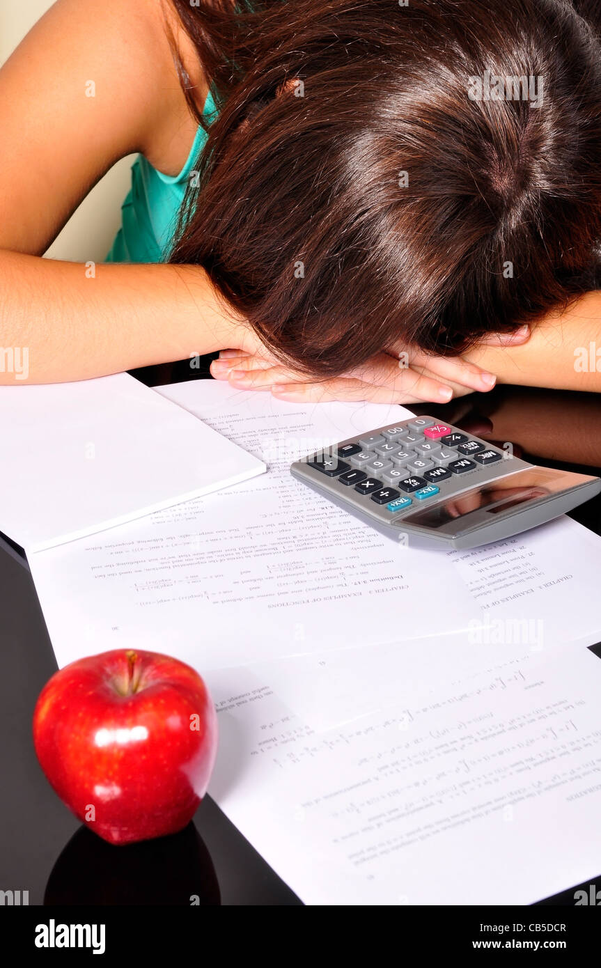Young woman, tired of studying, sleeping over maths exercises - Stock Image