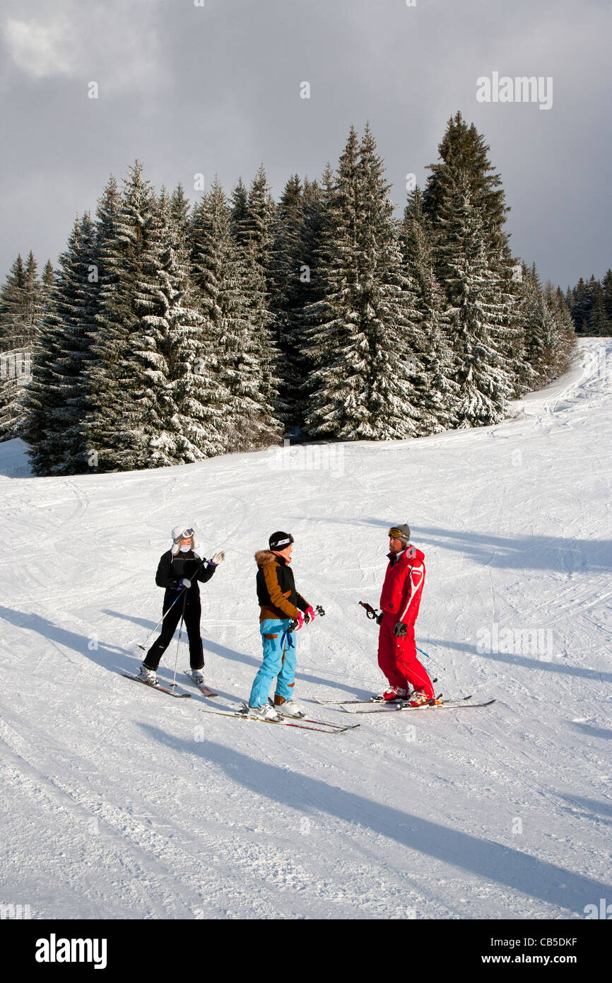 Ski instructor and skiers at Les Gets, Haute Savoie, Rhône-Alpes, France - Stock Image