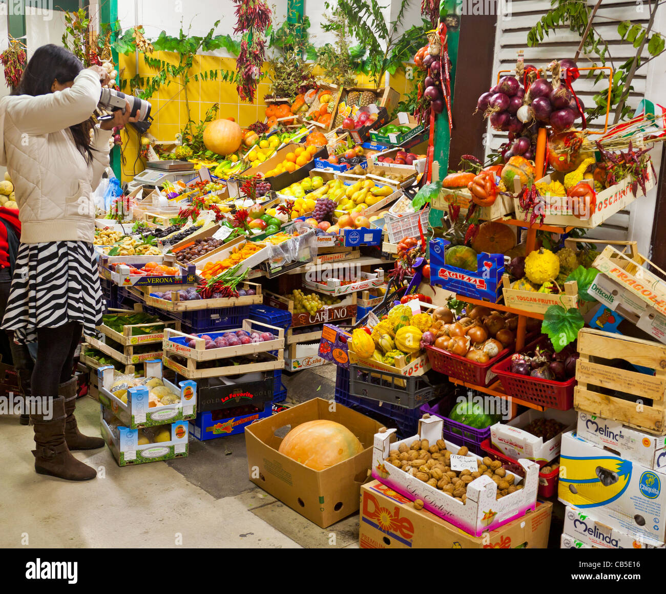 Young woman photographer taking a photograph in the Mercato centrale, Florence, Italy. fruit, vegetables, - Stock Image