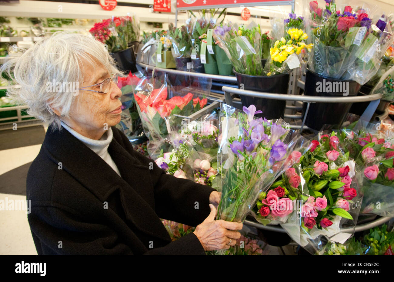 Elderly woman buying flowers stock photos elderly woman buying elderly lady buying flowers in a waitrose supermarket uk stock image izmirmasajfo
