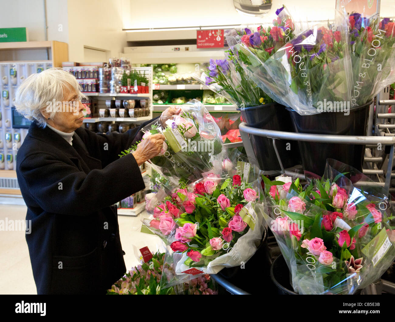 Elderly woman buying flowers stock photos elderly woman buying elderly lady buying flowers in a waitrose supermarket newmarket uk stock image izmirmasajfo