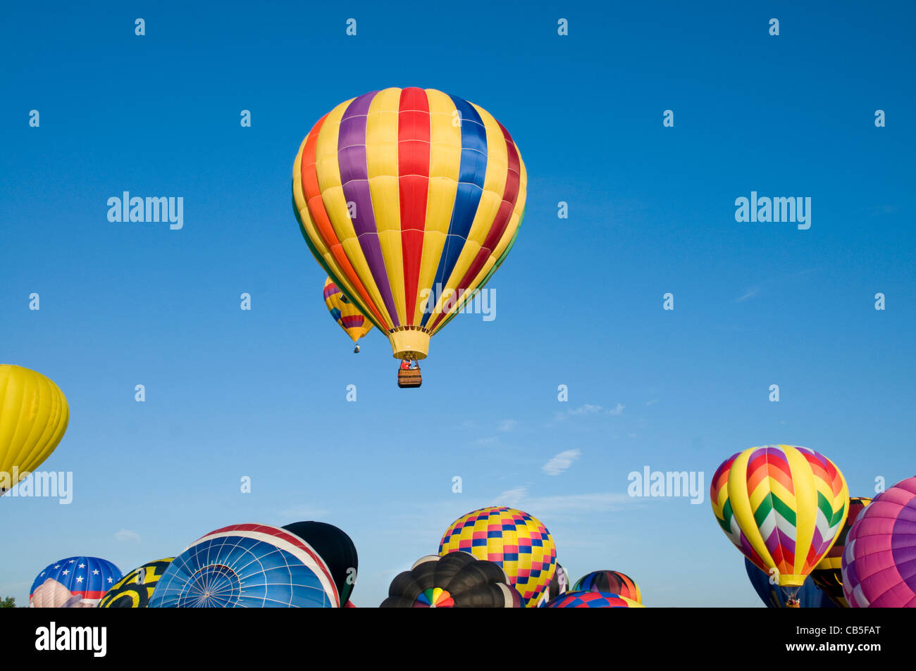 Hot-air balloons ascending over inflating ones on the ground - Stock Image