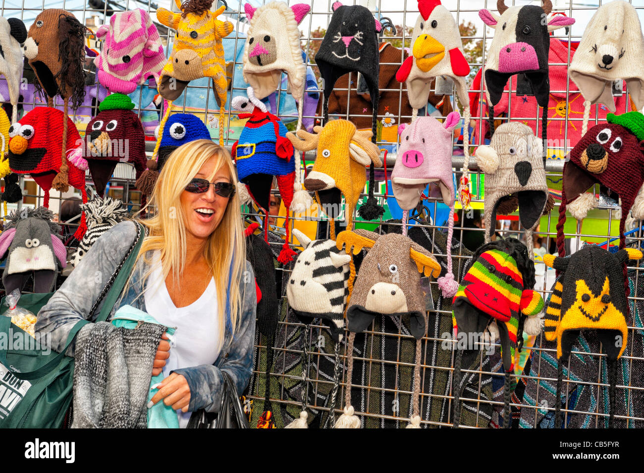 OCTOBER 22, 2011 - MERRICK, NY: Young woman looks at colorful animal knit hats on racks at booth, Merrick Street - Stock Image