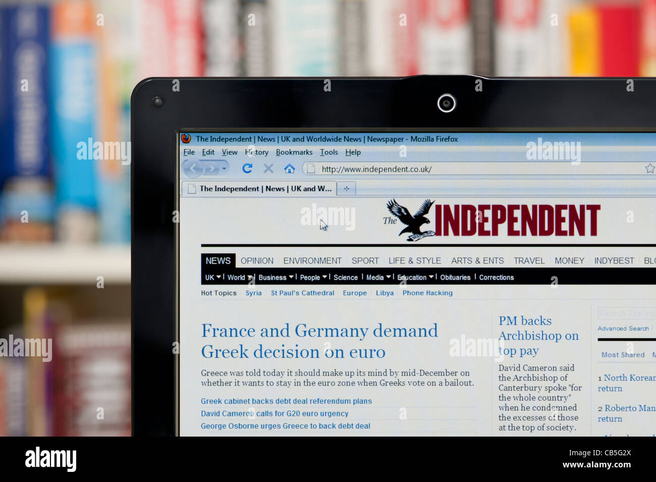The Independent website shot against a bookcase background (Editorial use only: print, TV, e-book and editorial - Stock Image