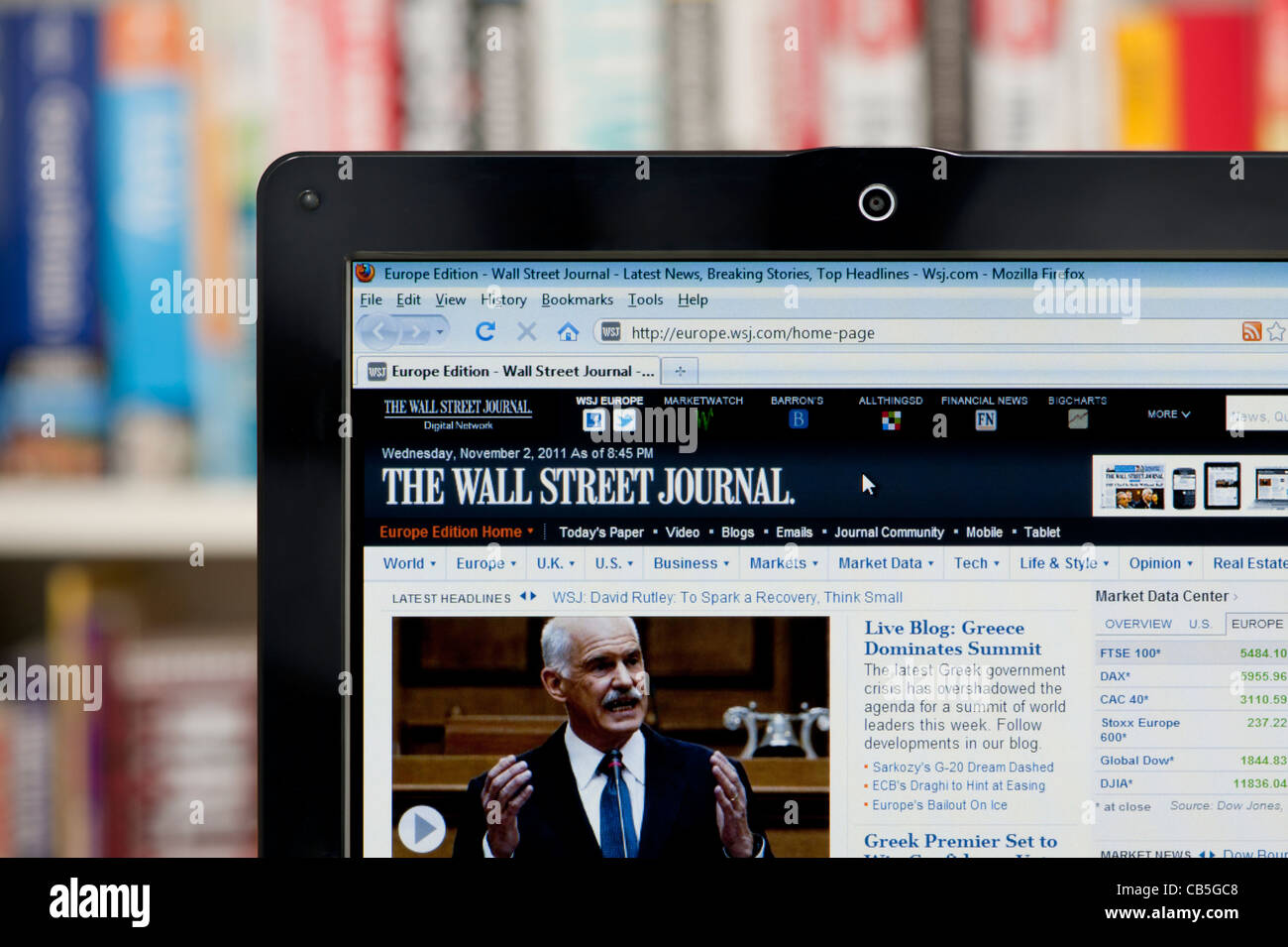The Wall Street Journal website shot against a bookcase background (Editorial use only: print,TV,e-book and - Stock Image