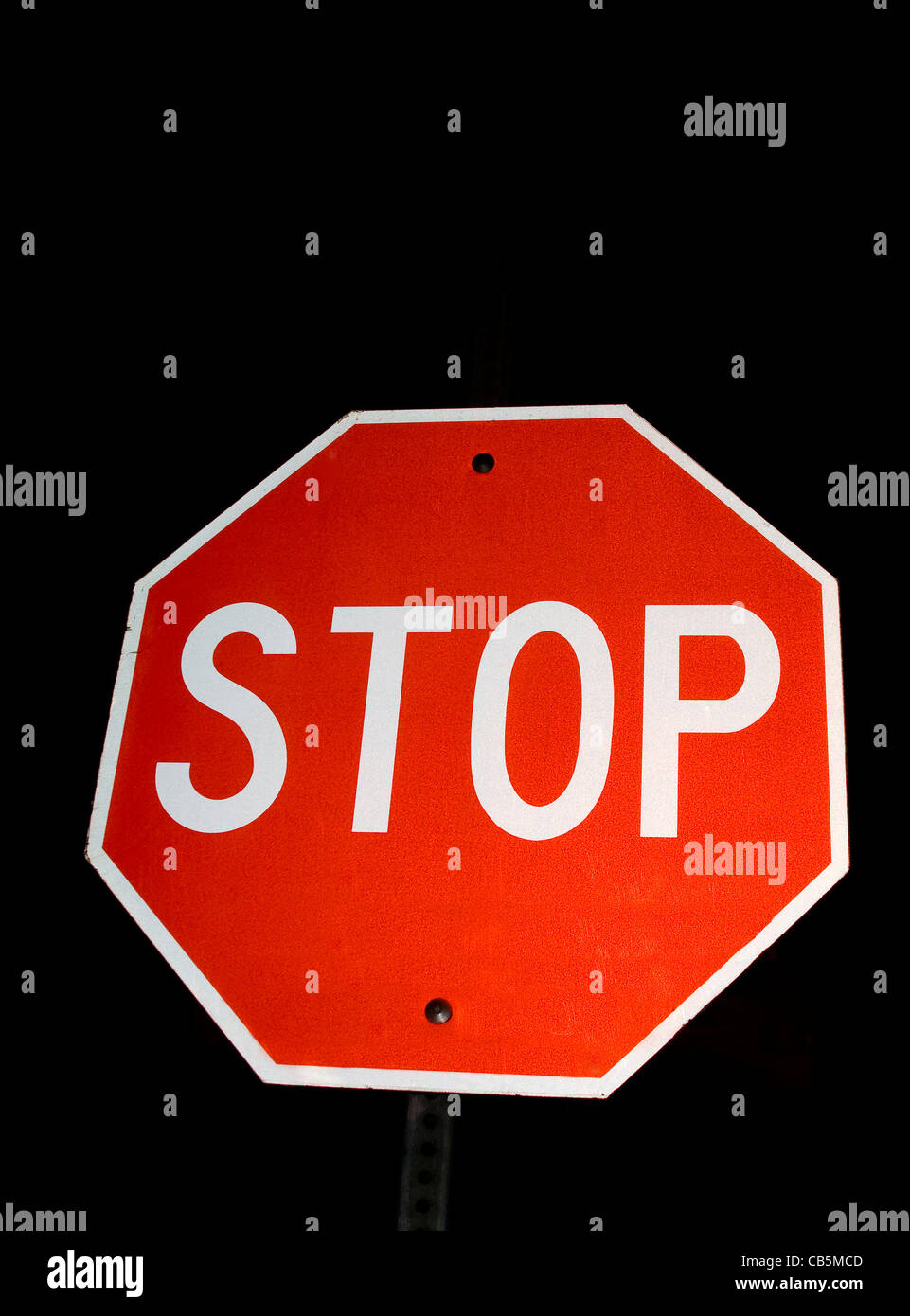 Bright Red Stop Sign at night - Stock Image