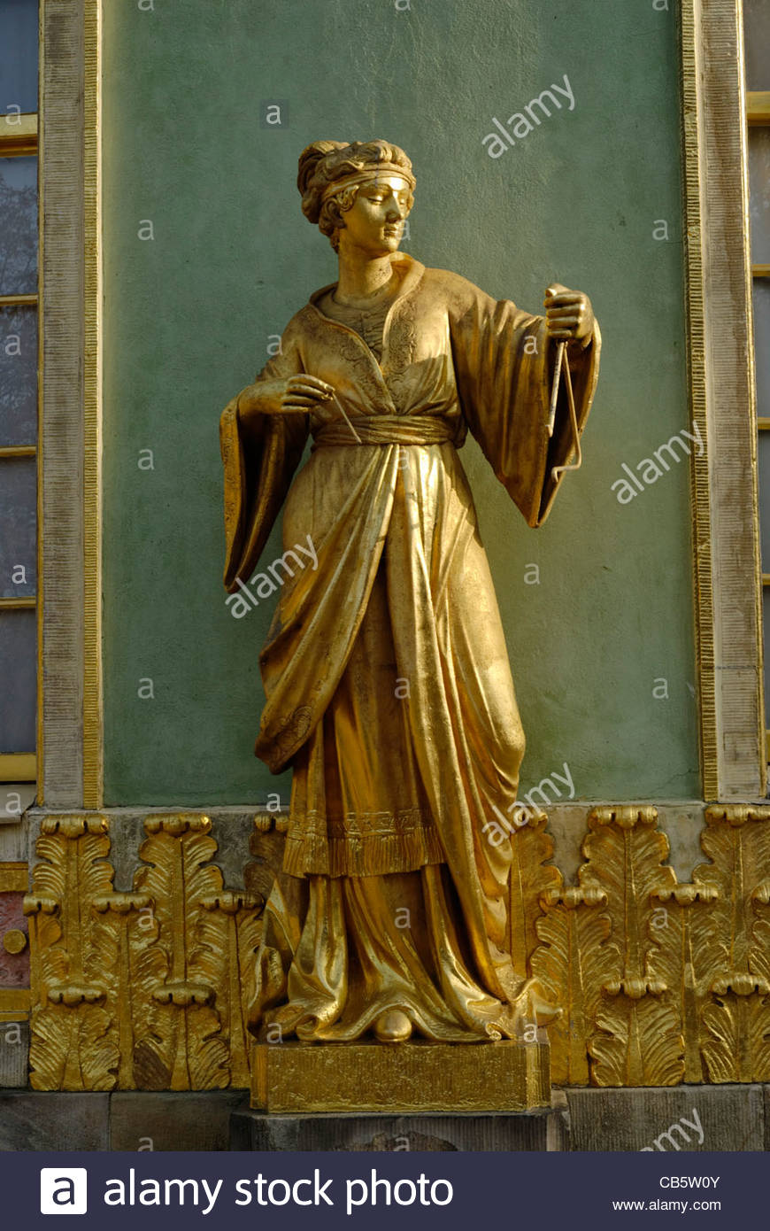 golden statue of a woman playing a triangle at The Chinese House, a garden pavilion in Sanssouci Park in Potsdam - Stock Image