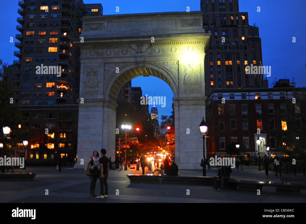 Arch with Empire State Building in distance lit up at Night in Washington Square Greenwich Village Manhattan New Stock Photo