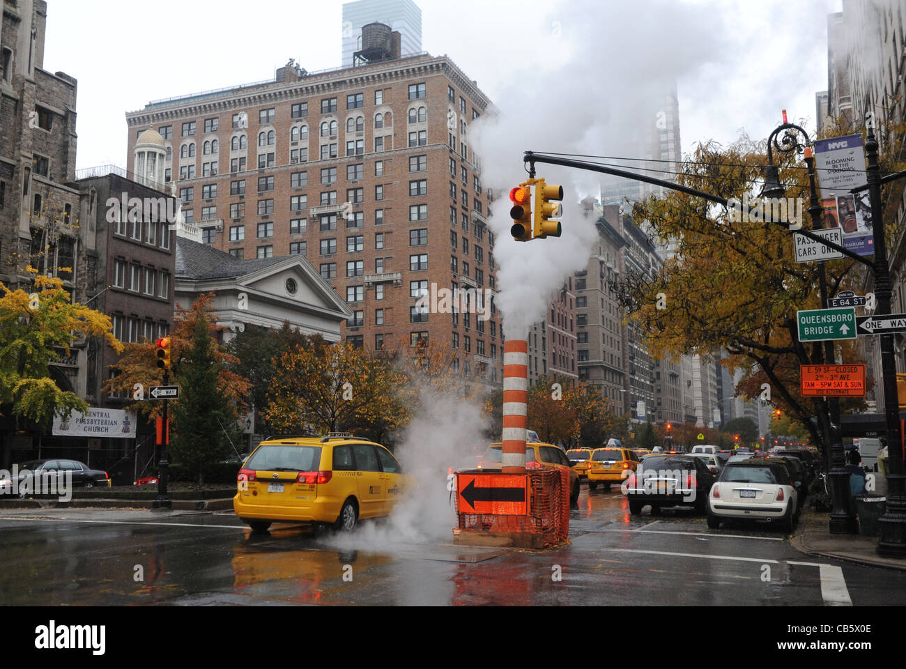 Steam rises from a standpipe in road on wet day Manhattan New York NYC USA - Stock Image
