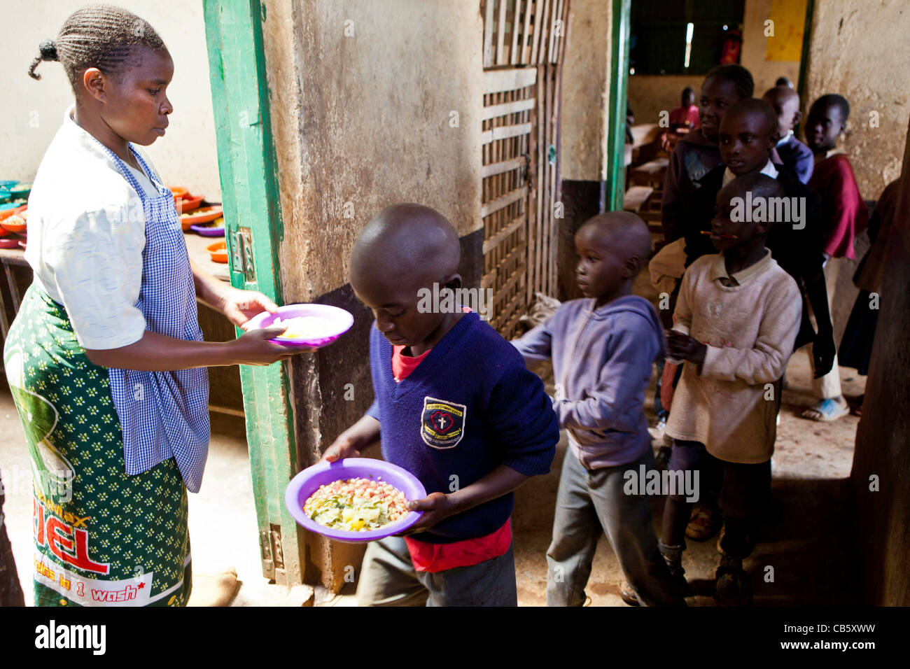School children receive freshly cooked food at Kibera School, Nairobi where an NGO runs a lunchtime feeding program. - Stock Image