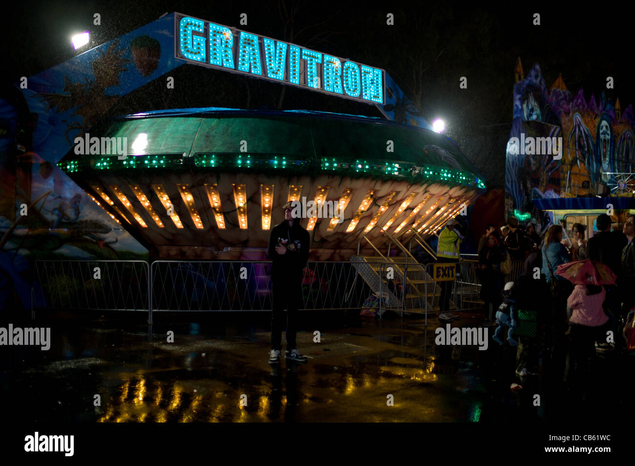 Customers wait in the Rain to Ride the GRAVITRON Amusment Park Ride- sci fi - Stock Image