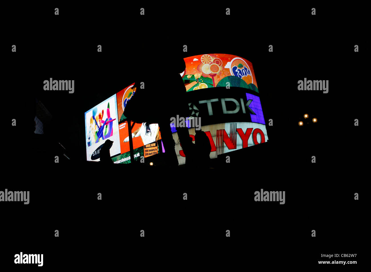 Silhouette in front of Piccadilly Circus advertising at night - Stock Image
