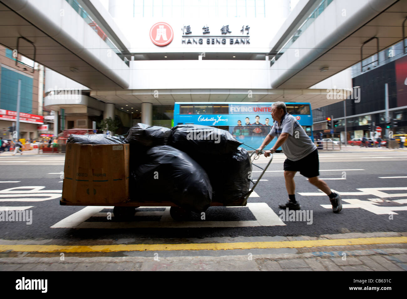 man pushes delivery cart past hang seng bank hq central district, hong kong island, hksar, china deliberate motion - Stock Image