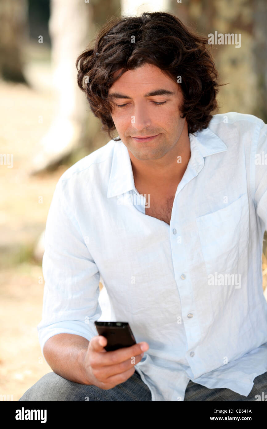 bloke reading an sms - Stock Image