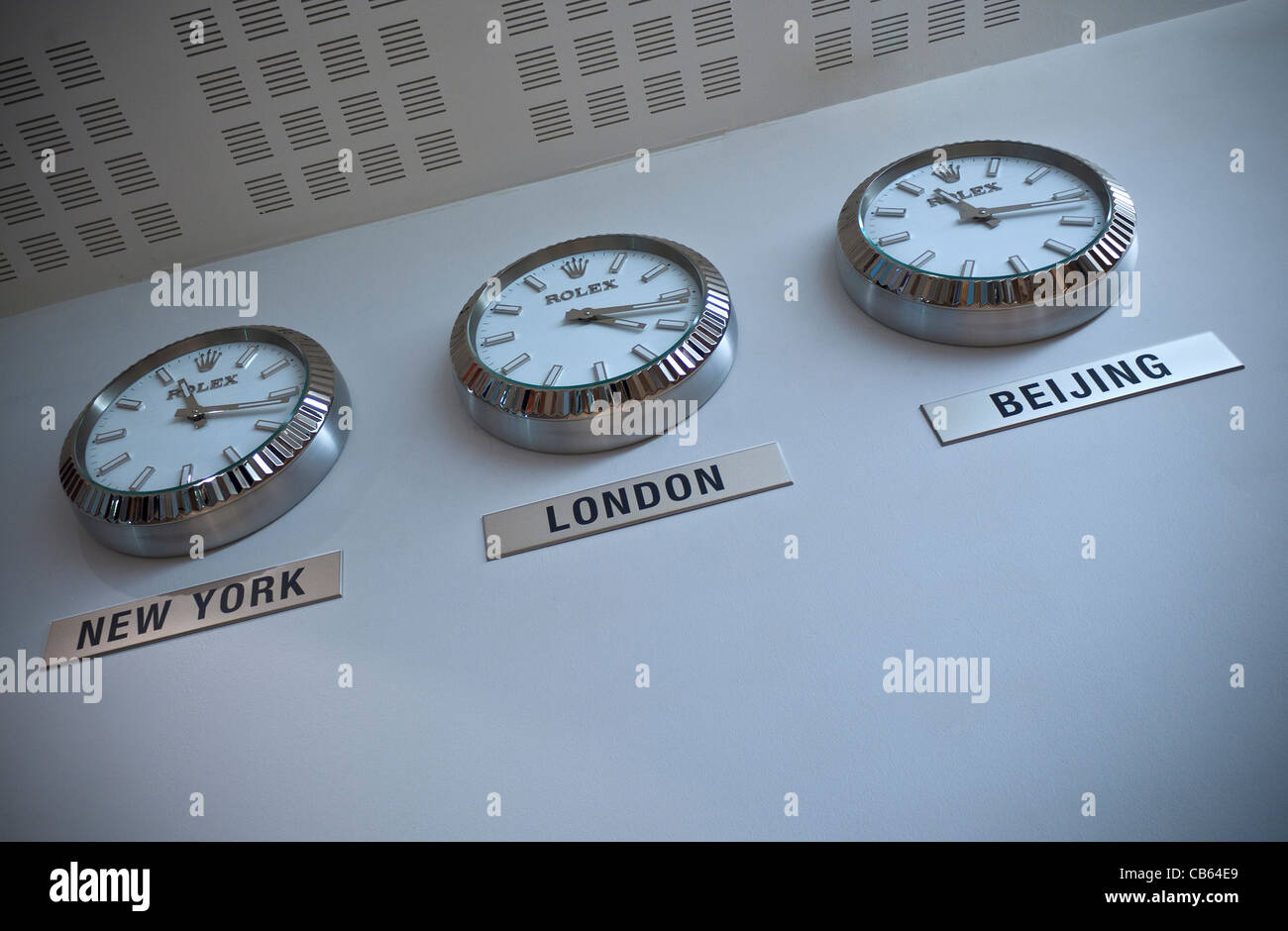 Three Rolex clocks on a white wall showing time zones in New York London and Beijing - Stock Image