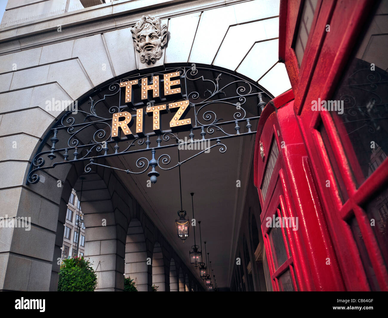 The Ritz Hotel London a luxury 5-star hotel in Piccadilly with preserved traditional red telephone boxes in foreground - Stock Image