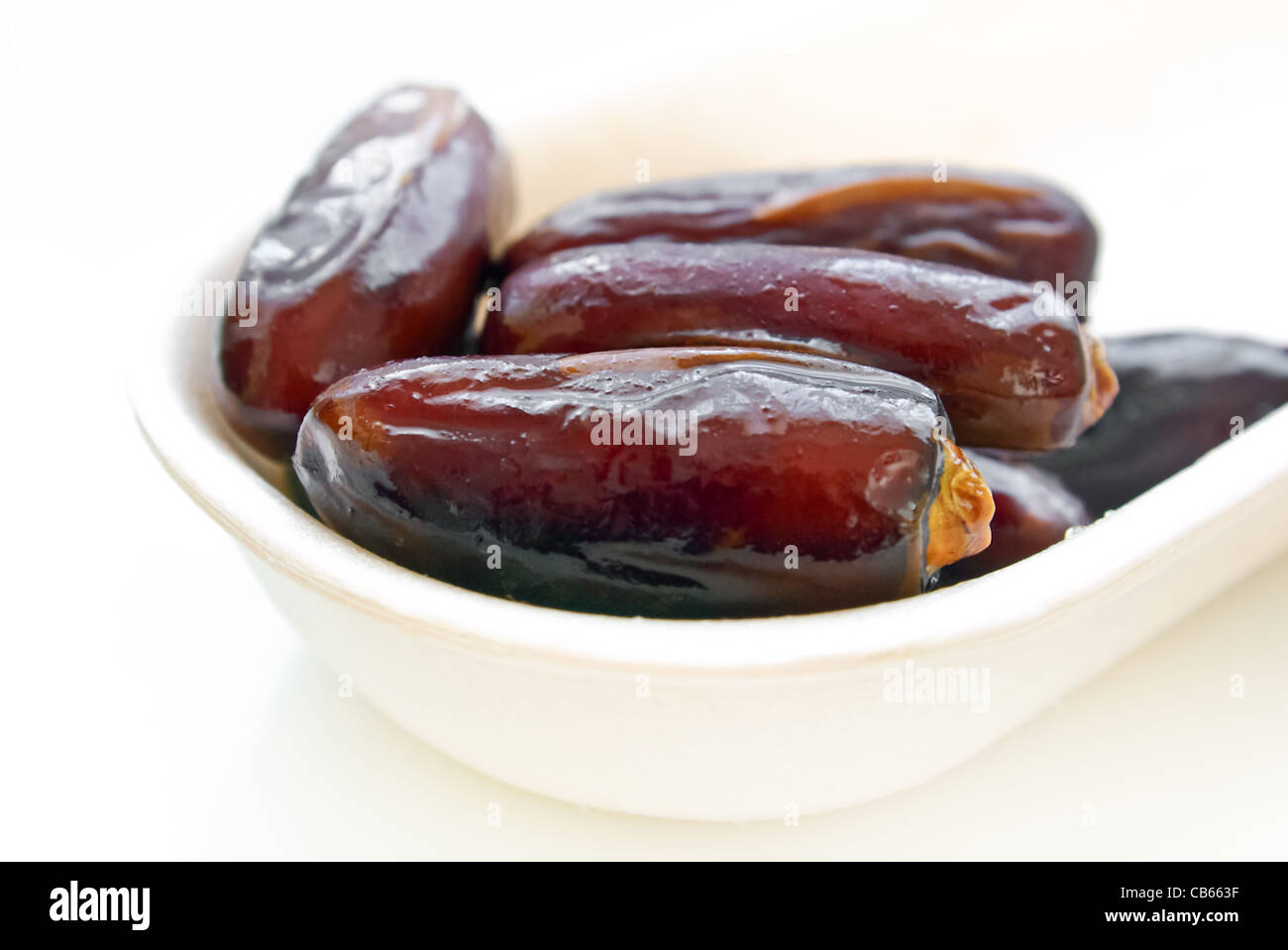 Macro of date fruits in a plate on white background - Stock Image