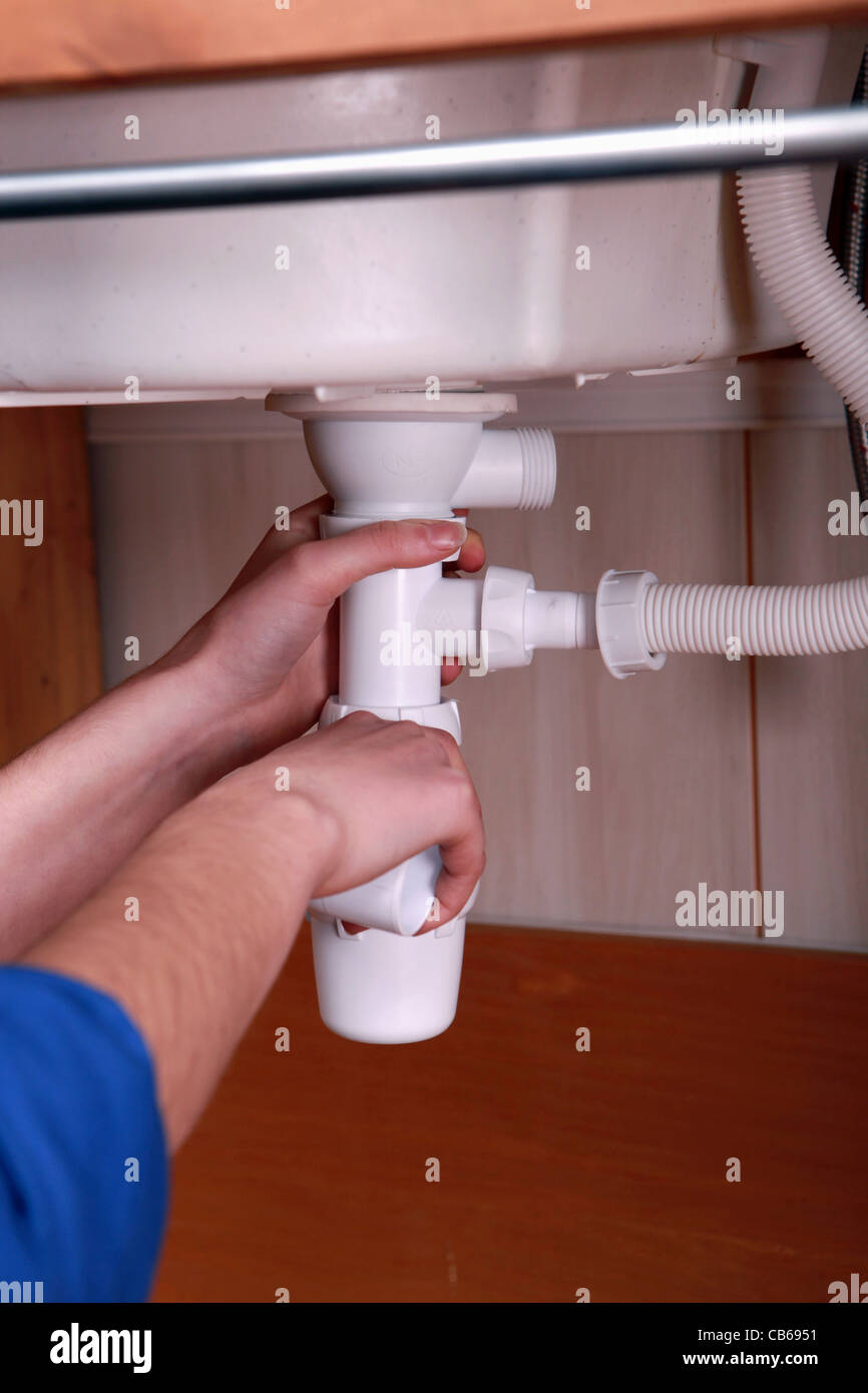Plumber Fitting The Waste Pipe To A Kitchen Sink Stock Photo Alamy