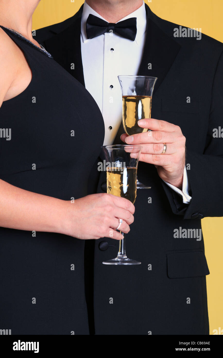 Photo of a couple in black tie evening dress holding a glass of champagne. - Stock Image
