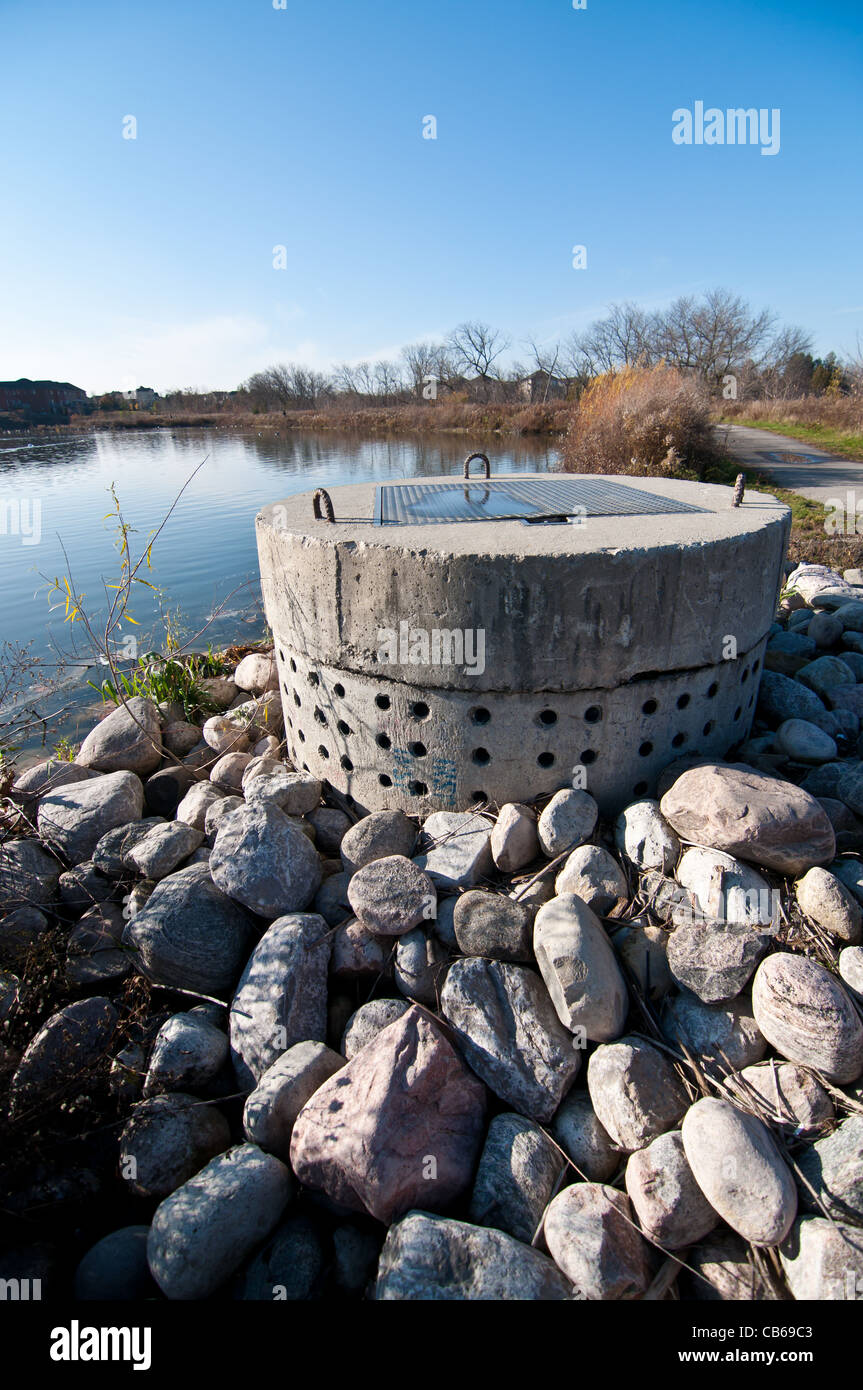 A perforated concrete pipe forms part of a stormwater management system in a suburban pond. Stock Photo