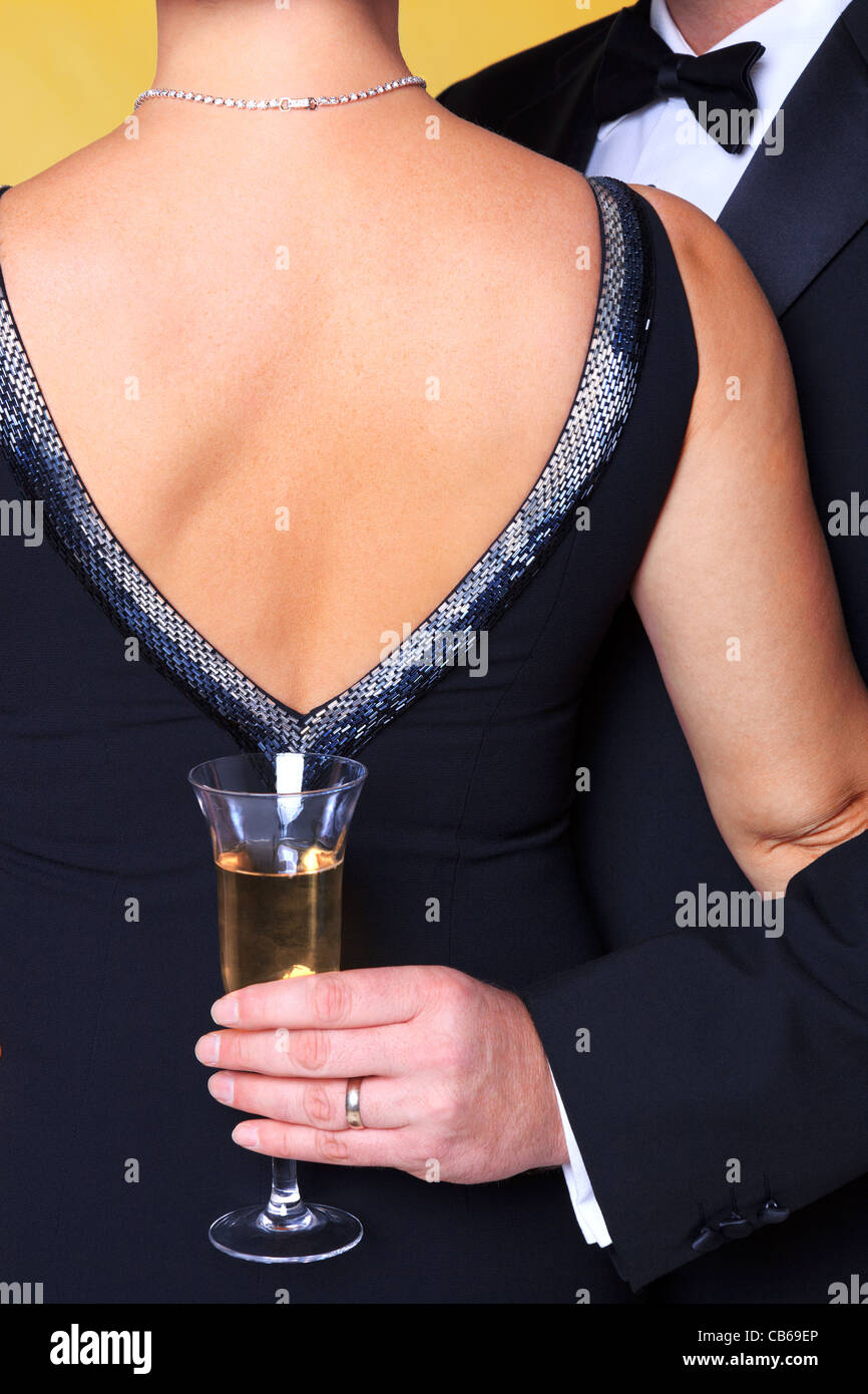 Photo of a couple in black tie evening wear, rear view of the womans back with the man holding a glass of champagne. - Stock Image