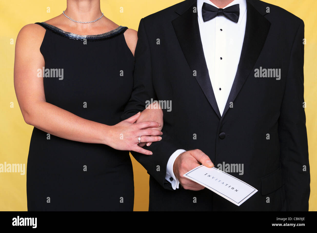 Photo of a couple in black tie evening wear, the man is holding an invitation. - Stock Image
