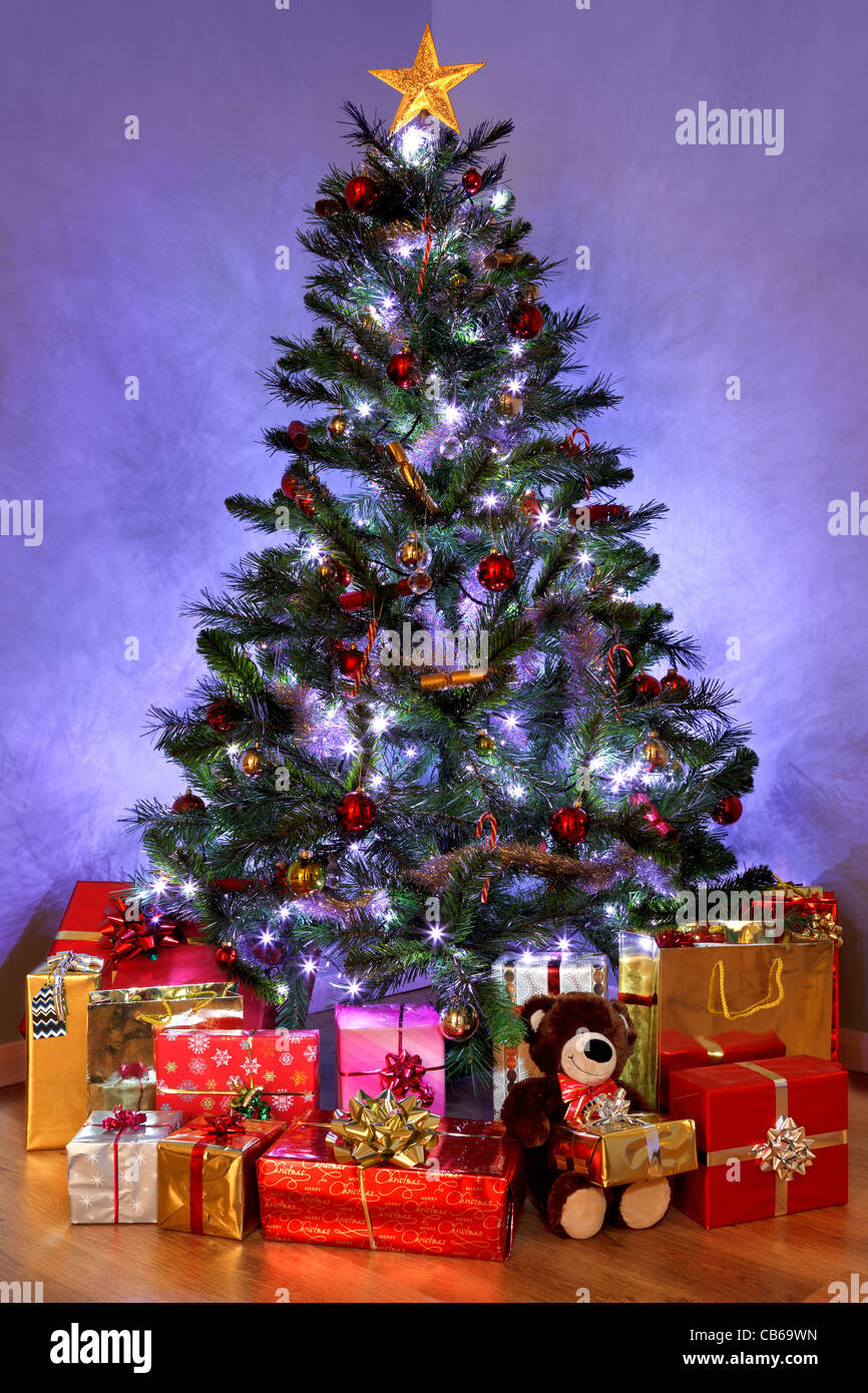 photo of a christmas tree with decorations and fairy lights surrounded by presents on a wooden floor