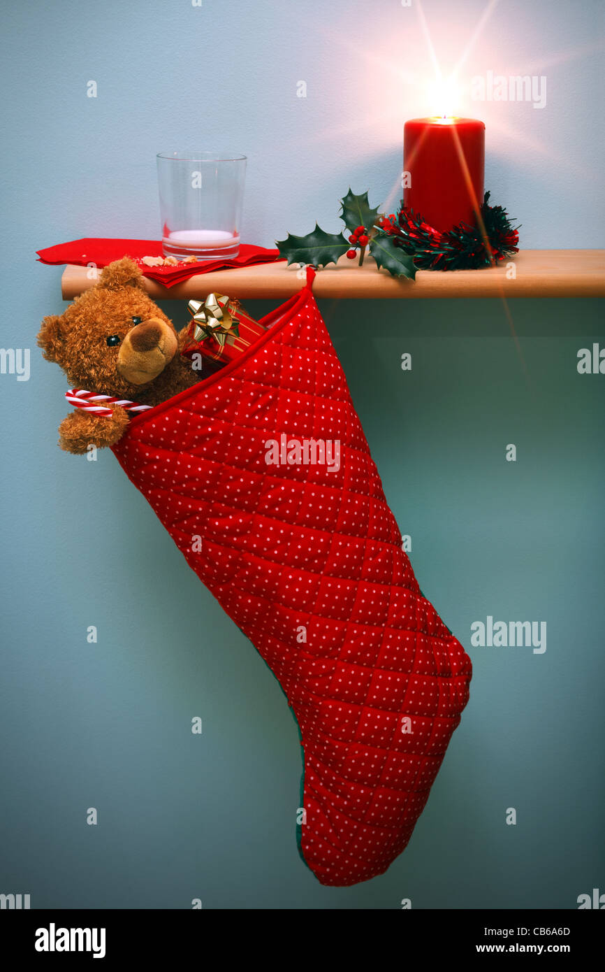 Photo of a Christmas stocking filled with presents and a candle surrounded by holly, - Stock Image