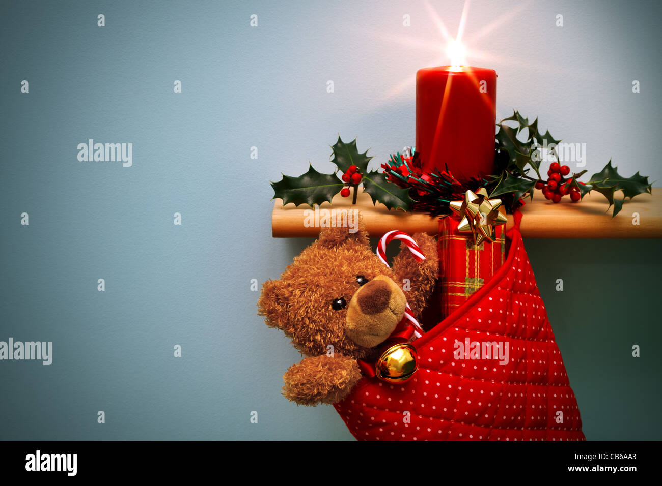 Photo of a Christmas stocking filled with presents and a candle surrounded by holly - Stock Image