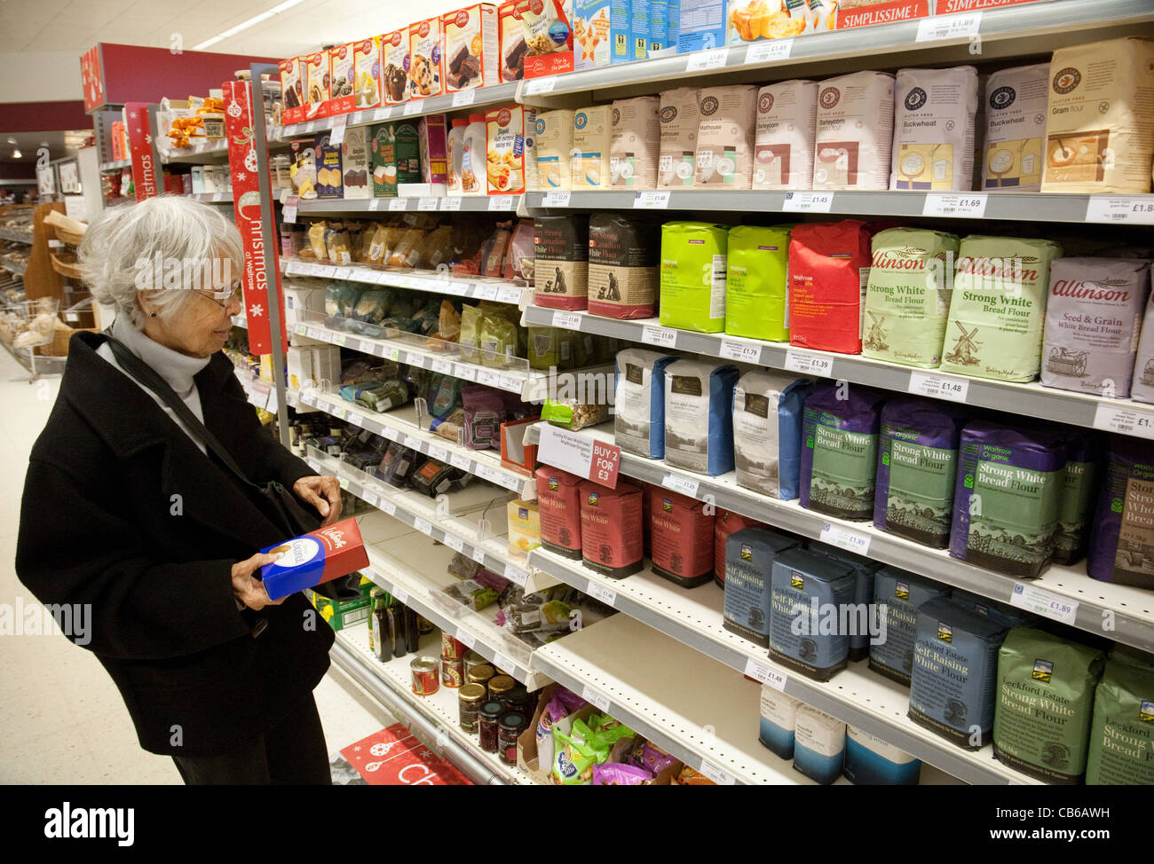 Old woman shopping for  flour in a supermarket aisle, UK - Stock Image