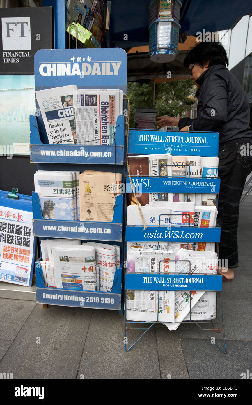 english and chinese language newspapers on wall street journal asia newspaper stall stand in downtown central district - Stock Image