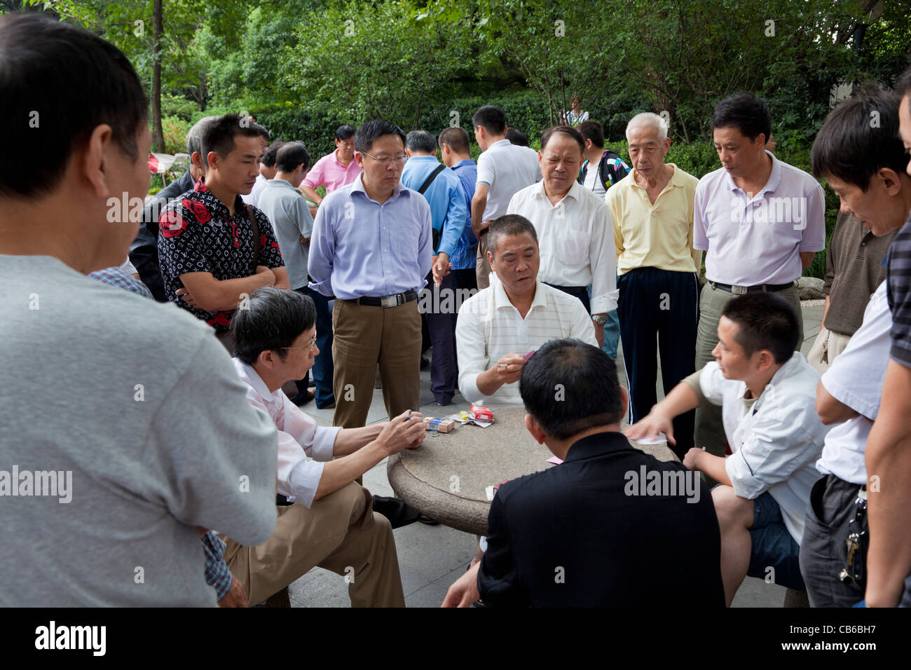 Chinese men playing cards in People's Park, Shanghai, PRC, People's Republic of China, Asia - Stock Image